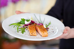 Cropped image of waitress displaying salmon dish in restaurant