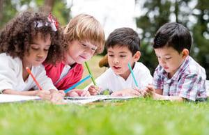Group of school kids coloring outdoors looking happy