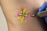 Hand tattooing colourful traveling concept on naked clear skin